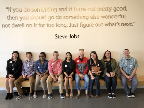 Group visiting Apple HQ with Digital Flagship. 8 participants seated beneath Steve Jobs quote.