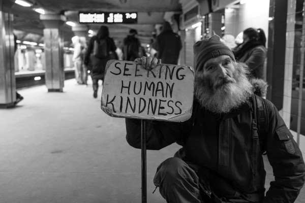 "Image of homeless gentleman holding a sign that reads ""Seeking Human Kindness."""