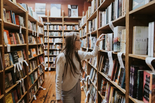 A young woman examines books on a shelf.