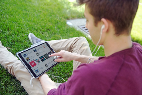 Student sitting on the grass looking at and selecting a podcast on his ipad