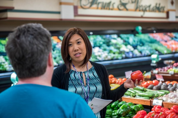 educator speaks to a person in a grocery story