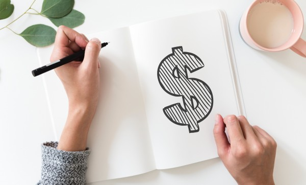 Image of a dollar sign sketch in a notebook