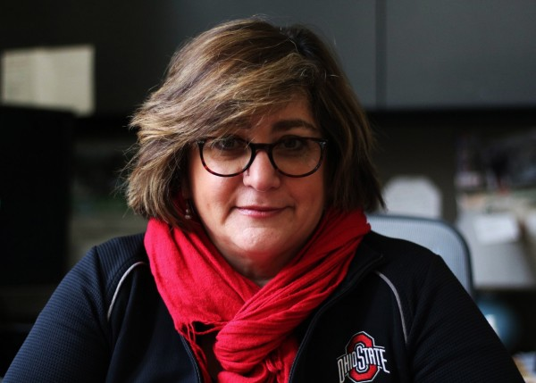 A photograph of Nicole Kraft, who is wearing a red scarf and a jacket with The Ohio State University logo.