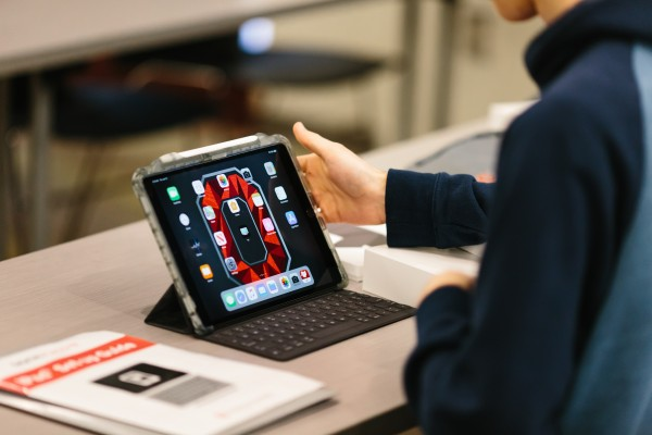 Student holding iPad displays Block O wallpaper in red on grey backdrop