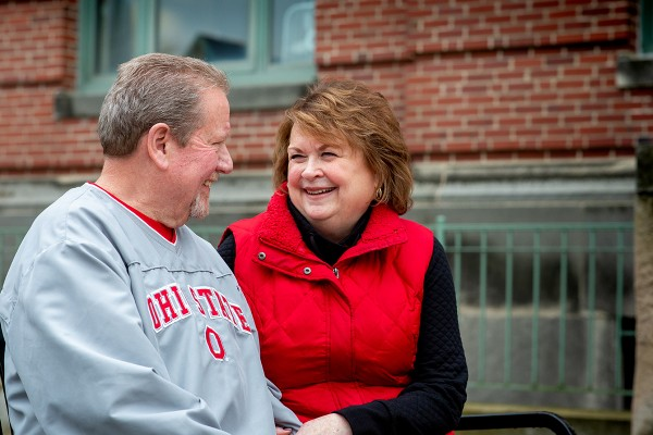 Senior couple sit on a bench outside, wearing red Ohio State gear and smiling at each other.
