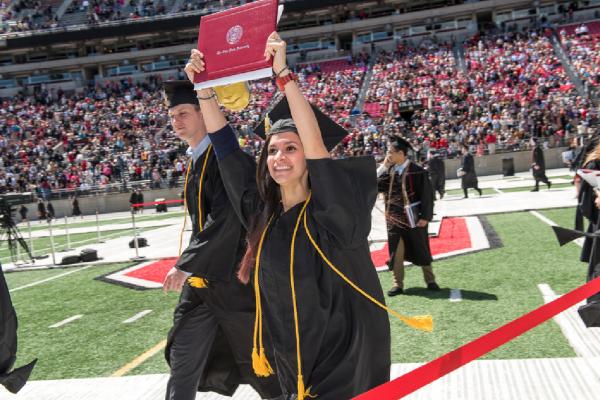 Ohio State graduate holding diploma overhead.