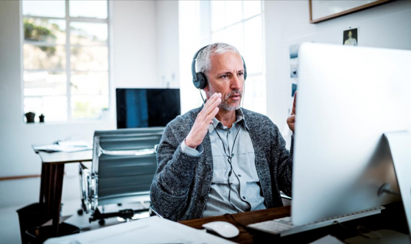 Man with headset gesturing at computer screen
