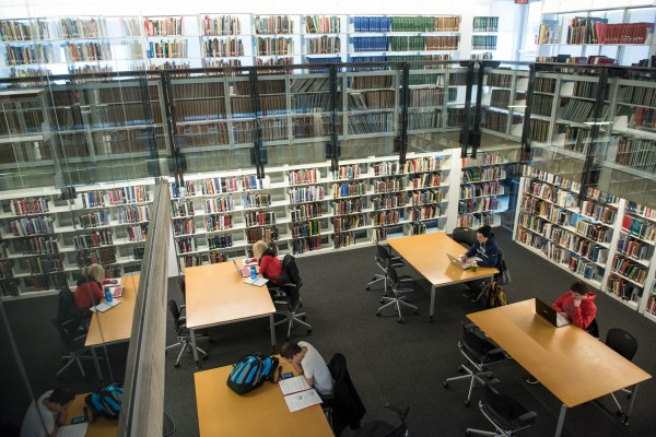 Four students study at separate tables amid the stacks in Thompson Library