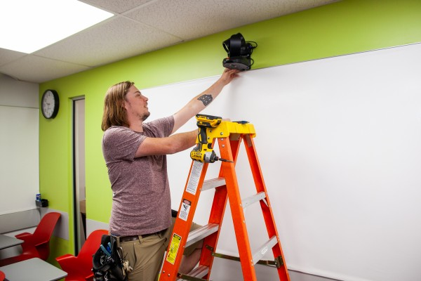 a staff member standing on a ladder adjusts a camera mounted on the wall of a classroom