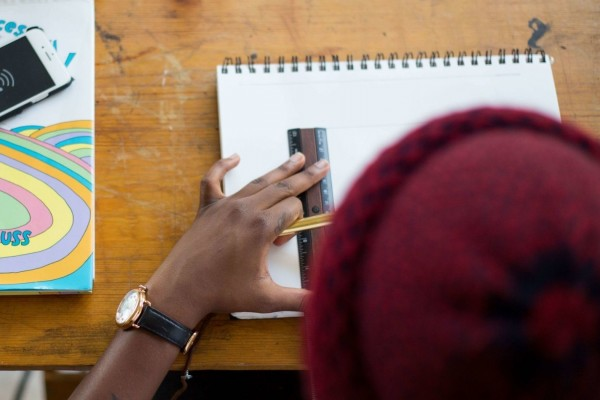 A person lines up a ruler on a drawing notebook, pencil ready to begin sketching