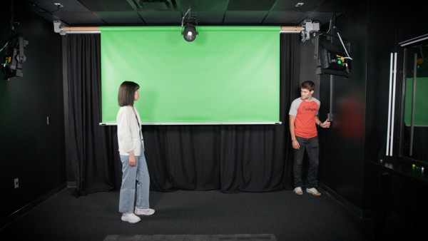 A woman wearing a white jacket watches as a young man lowers a green screen from the ceiling inside a video studio.