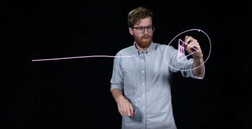Man drawing a pink arrow on the clear board